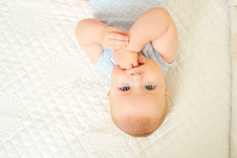 Neonato che esamina gli occhi mentre trovandosi su un fondo bianco fotografia stock libera da diritti