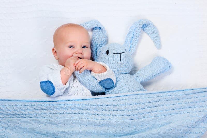 Neonato che gioca con il giocattolo del coniglietto tricottato blu fotografia stock