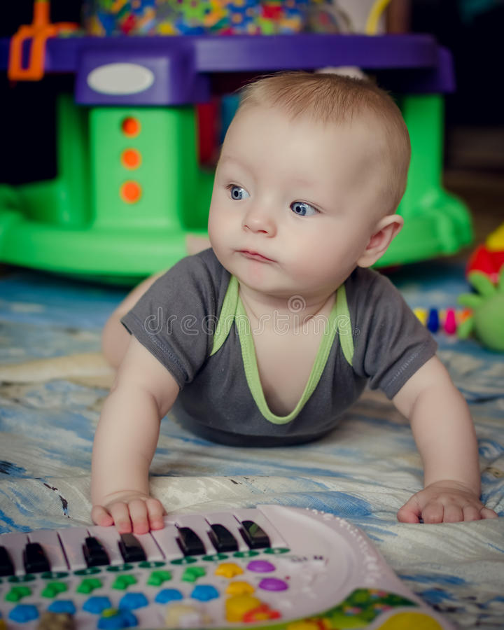 Neonato che gioca con il giocattolo del piano fotografia stock