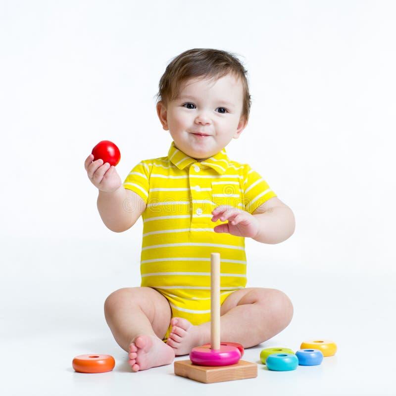 Neonato che gioca con il giocattolo della piramide immagine stock