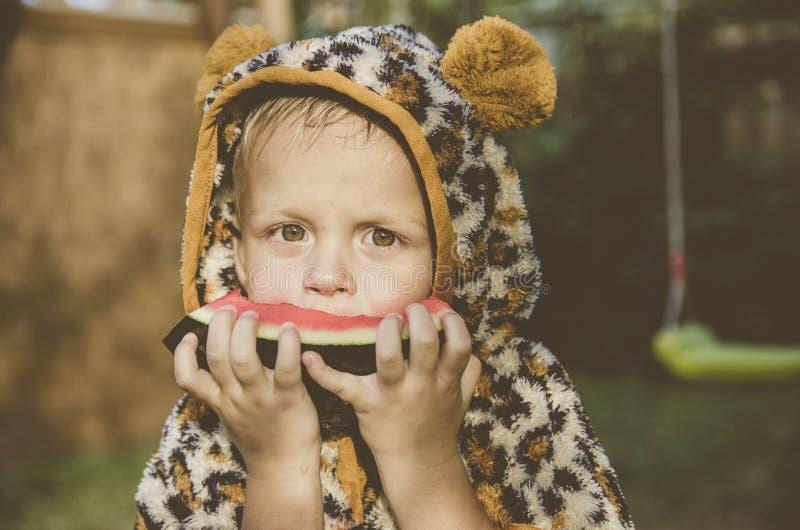 Neonato che gioca nel giardino Il ragazzo che mangia anguria fotografia stock libera da diritti