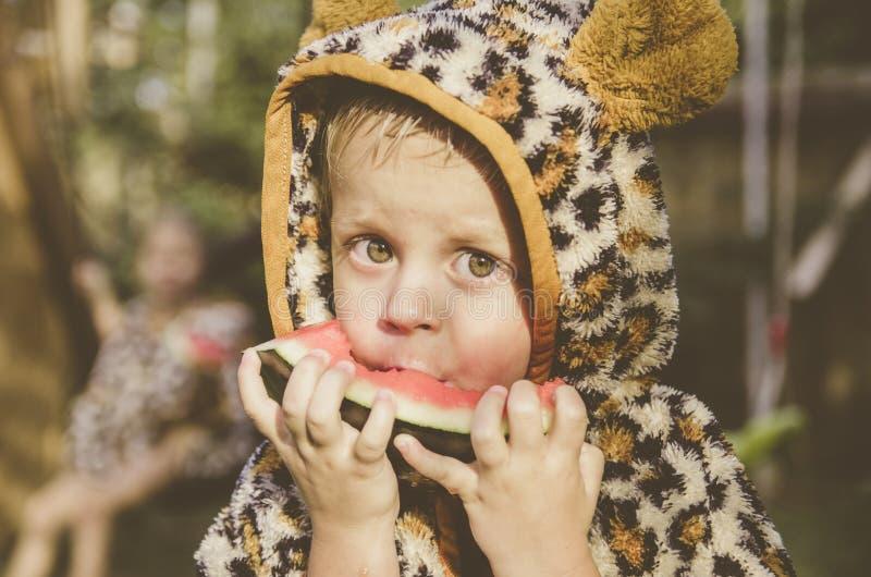 Neonato che gioca nel giardino Il ragazzo che mangia anguria fotografie stock libere da diritti