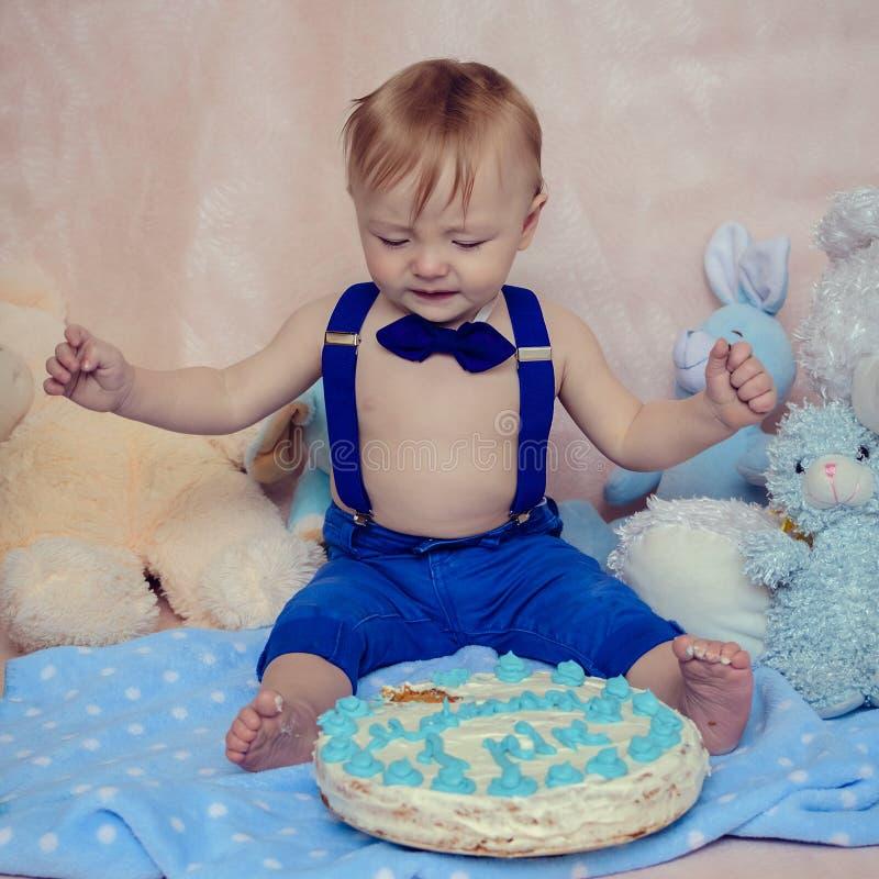 Neonato che grida mentre mangiando il suo dolce della festa di compleanno immagine stock