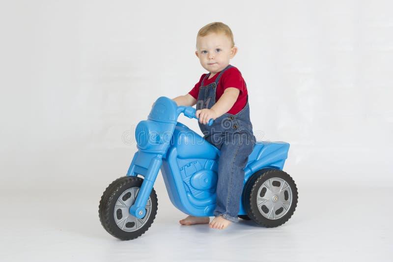Neonato che guida il suo motorino di plastica fotografia stock libera da diritti