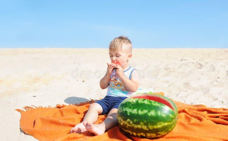 Neonato che mangia la fetta dell'anguria contro il fondo della spiaggia fotografia stock