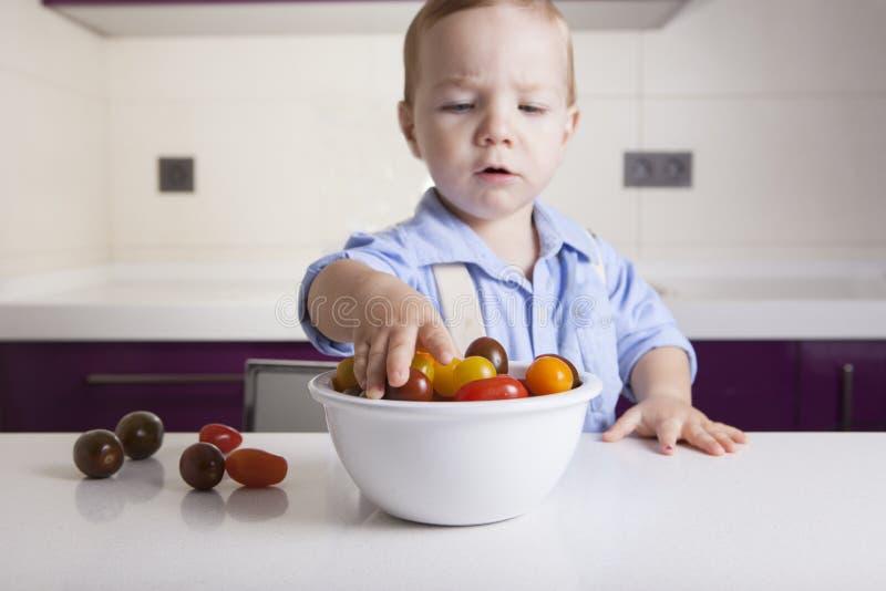 Neonato che prende i pomodori ciliegia variopinti maturi fotografia stock libera da diritti