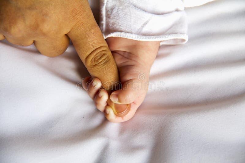 Neonato che tiene il suo dito delle madri immagine stock libera da diritti