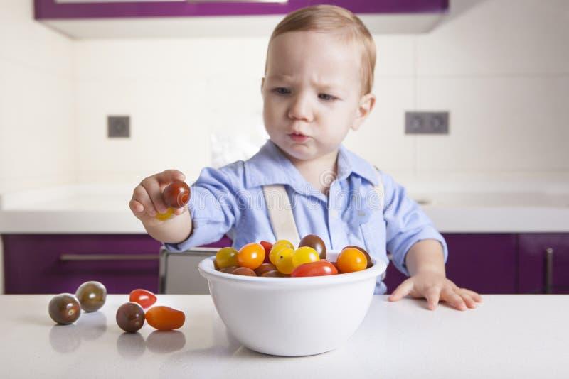 Neonato che tiene un tomatoe variopinto maturo della ciliegia fotografie stock libere da diritti