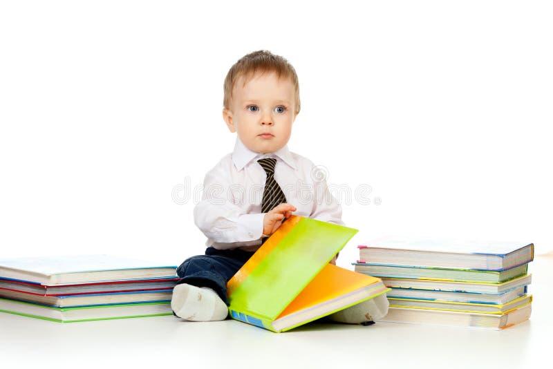 Neonato con i libri sopra bianco immagine stock