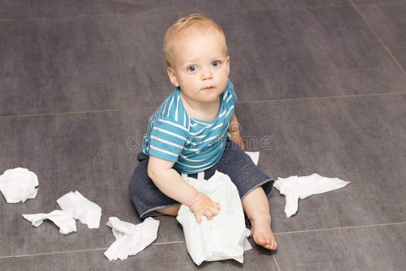 Neonato con i occhi spalancati sveglio che si siede con le strofinate sparse sul pavimento immagini stock