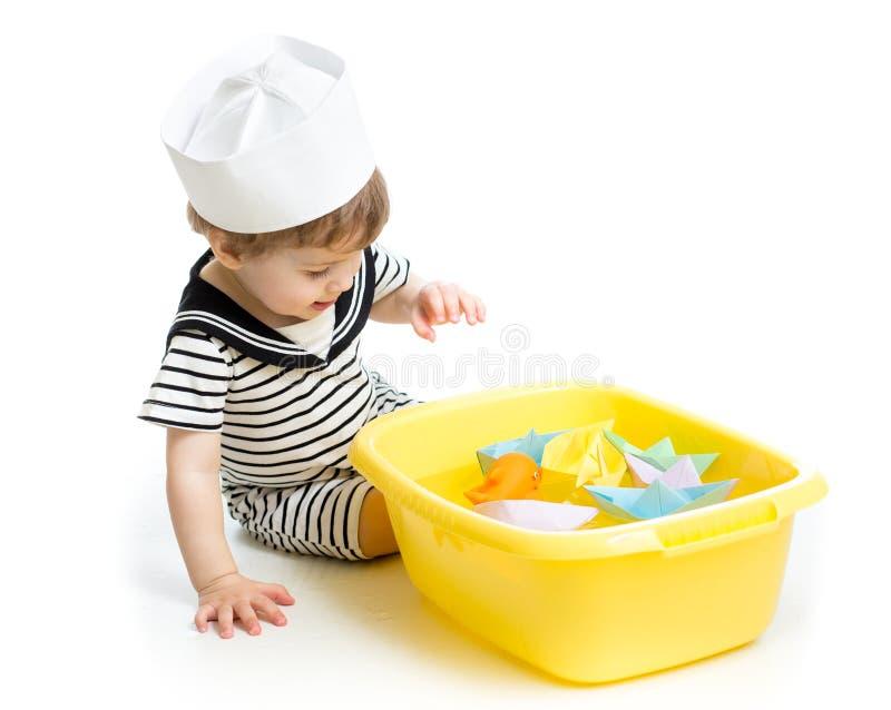 Neonato con il cappello del marinaio che gioca con le barche di carta fotografia stock