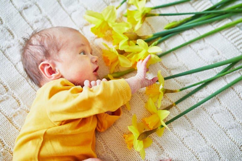 Neonato con il mazzo di narciso giallo immagini stock