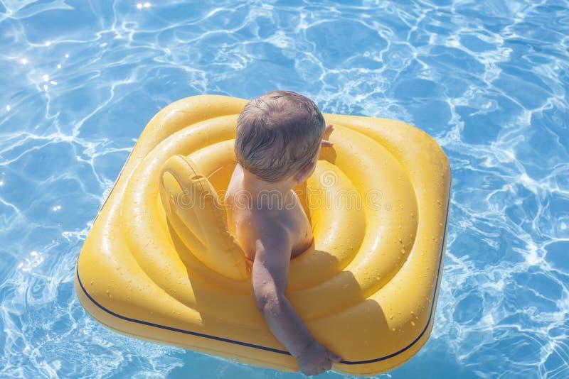 Neonato con l'anello di gomma giallo sulla piscina fotografia stock