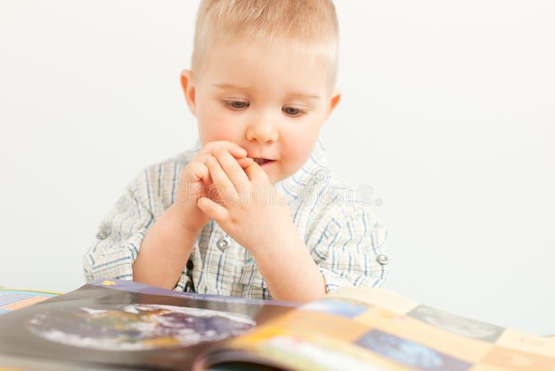 neonato curioso che studia con il libro immagini stock