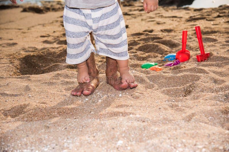 Neonato della famiglia e passeggiata felici del padre a piedi nudi sulla spiaggia di sabbia immagine stock libera da diritti