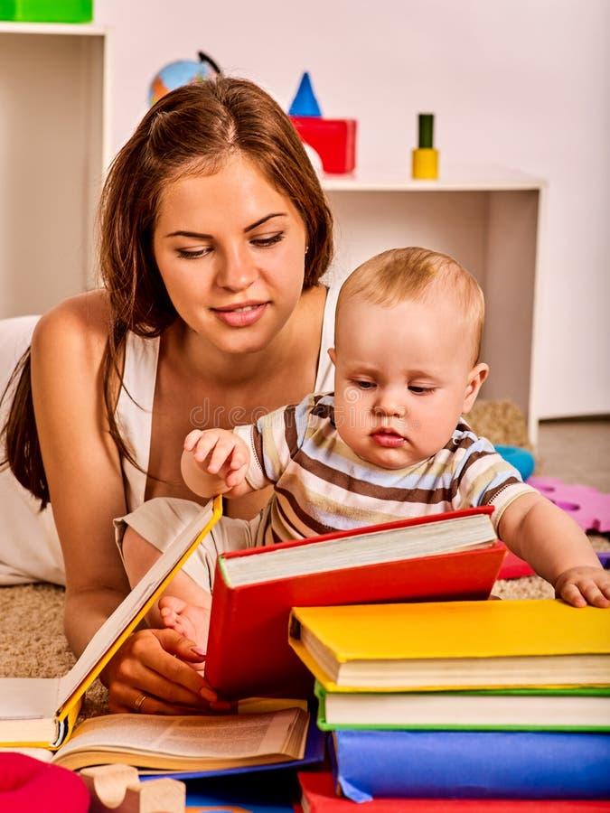Neonato della madre e del bambino che si trova sul pavimento e sul libro colto immagini stock