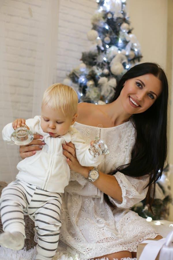Neonato di 1 anno sveglio e sua bella la madre che posano in nuovo fotografie stock
