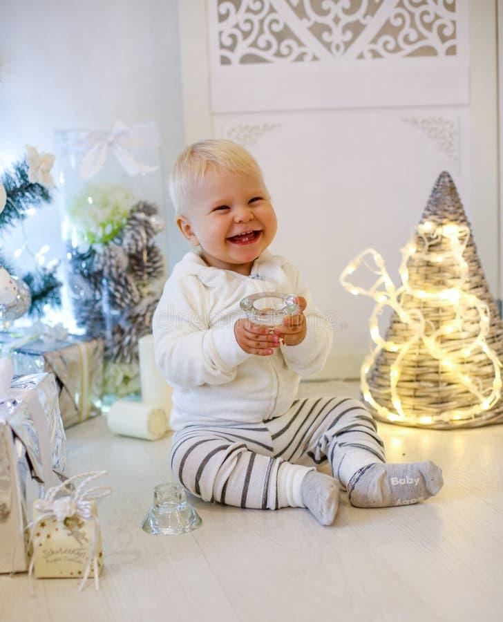 Neonato di 1 anno sveglio in vestiti accoglienti, posanti durante il nuovo anno dicembre fotografia stock libera da diritti