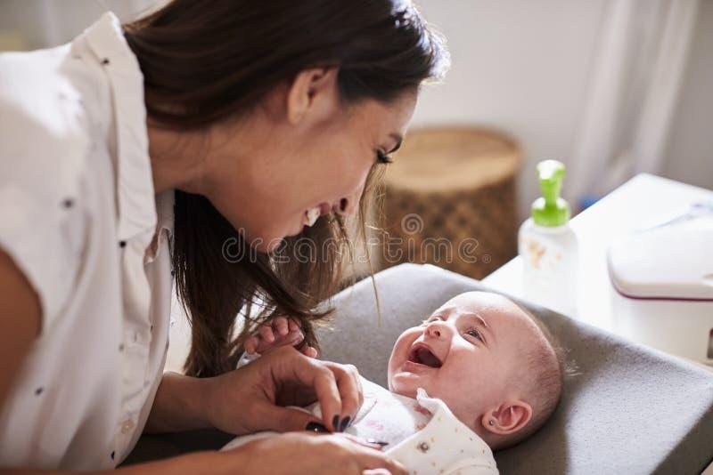 Neonato di quattro mesi felice che si trova sulla tavola cambiante che cerca la sua mummia, fine su fotografie stock
