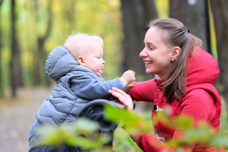 Neonato di un anno nel parco di autunno con sua madre fotografie stock