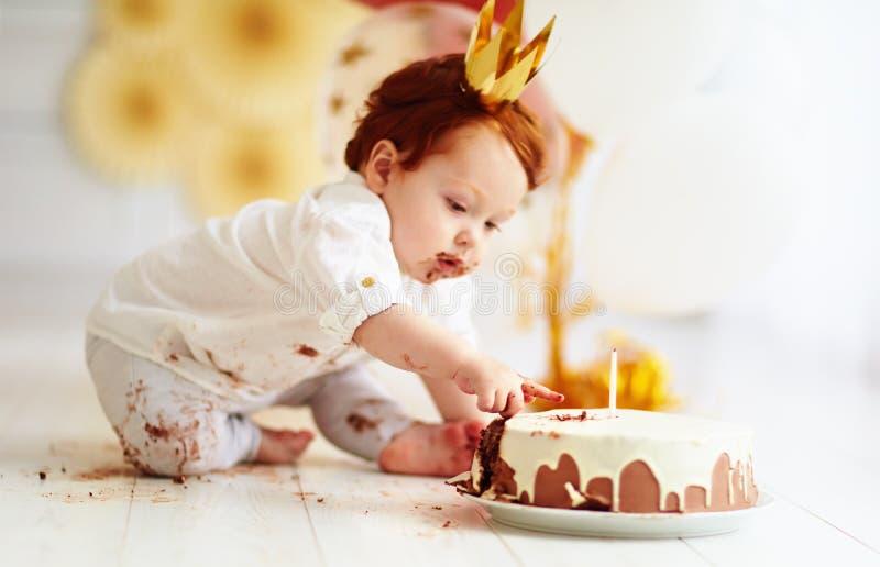 Neonato divertente curioso che colpisce dito in sua prima torta di compleanno fotografia stock