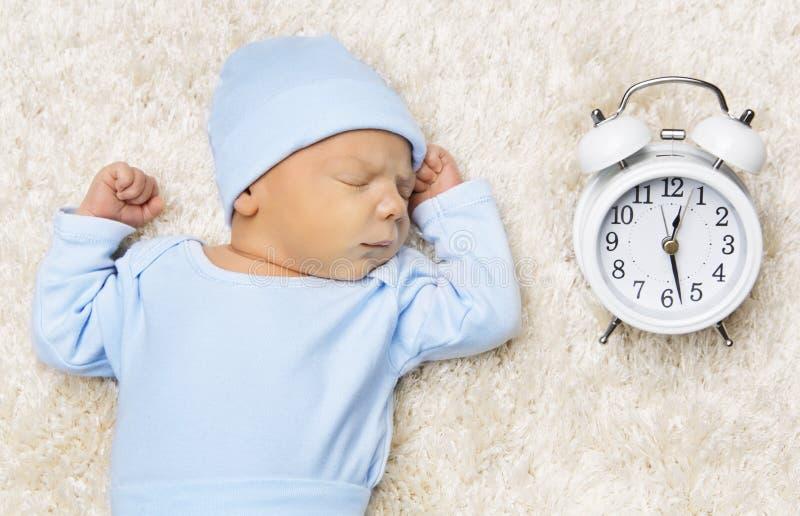 Neonato ed orologio addormentati, sonno neonato a letto fotografia stock libera da diritti