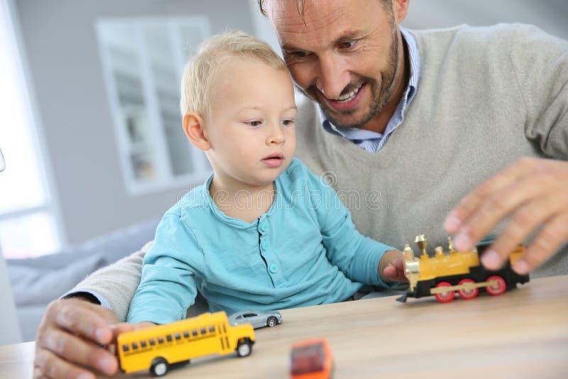 Neonato ed suo padre che giocano con le automobili immagini stock libere da diritti