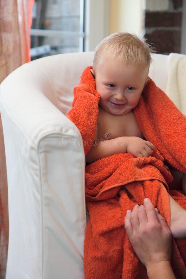 Neonato felice adorabile in asciugamano arancio immagine stock