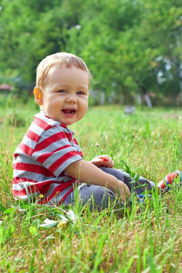 Neonato felice che si siede sul campo verde di estate immagine stock libera da diritti