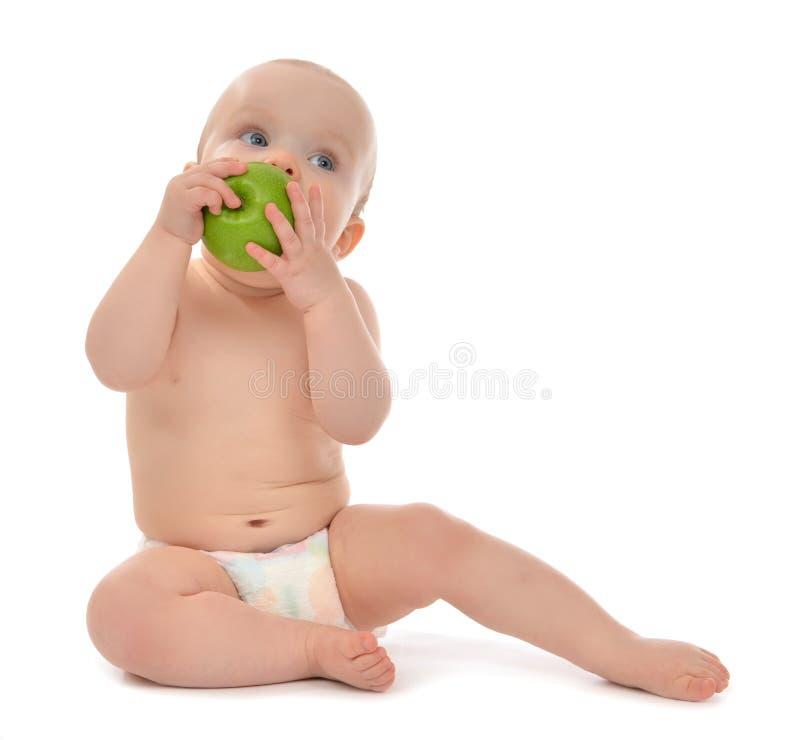 Neonato felice del bambino che si siede in pannolino e che mangia mela verde fotografia stock