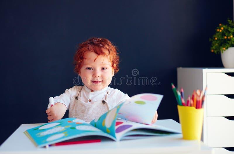 Neonato felice della testarossa che assorbe libro di sviluppo allo scrittorio fotografia stock