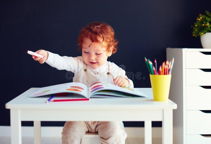 Neonato felice della testarossa che assorbe libro di sviluppo allo scrittorio immagine stock