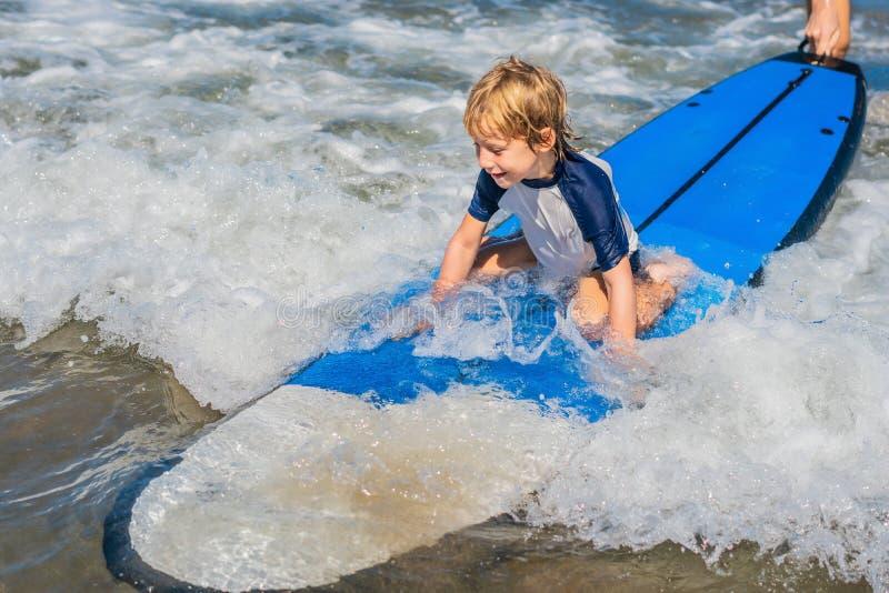 Neonato felice - giovane giro del surfista sul surf con divertimento sul mare immagini stock libere da diritti