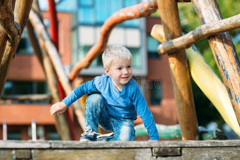 Neonato felice sveglio con capelli biondi divertendosi sul campo da giuoco fotografie stock