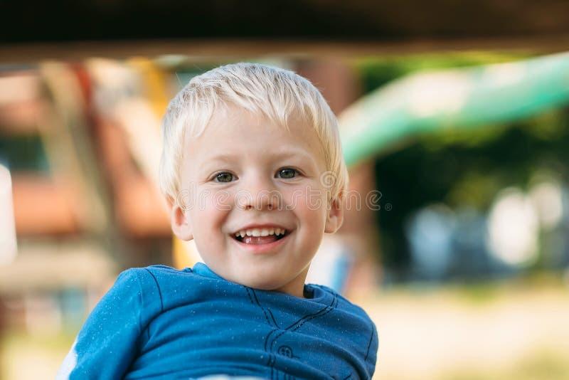 Neonato felice sveglio con capelli biondi divertendosi sul campo da giuoco fotografia stock libera da diritti