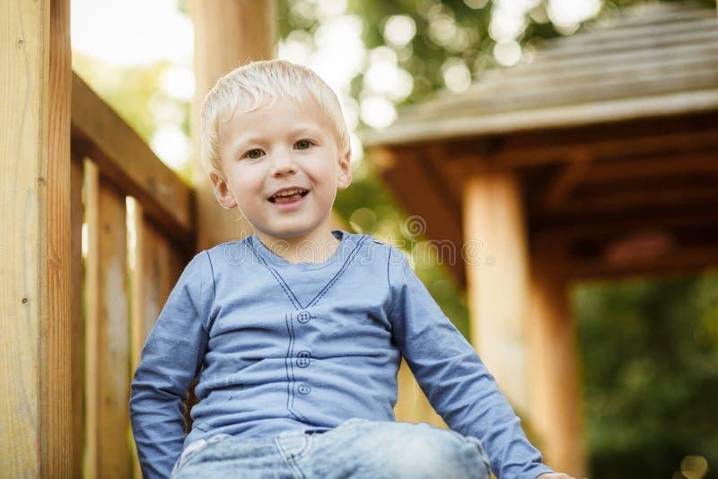 Neonato felice sveglio con capelli biondi divertendosi sul campo da giuoco immagine stock