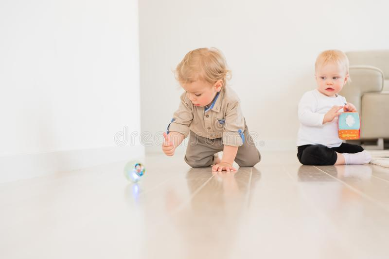 Neonato infantile sveglio che striscia sul pavimento a casa e che gioca con la palla variopinta fotografie stock libere da diritti