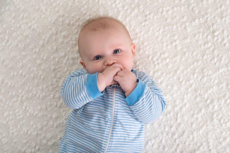 Neonato in pigiami a strisce blu e bianchi fotografia stock libera da diritti