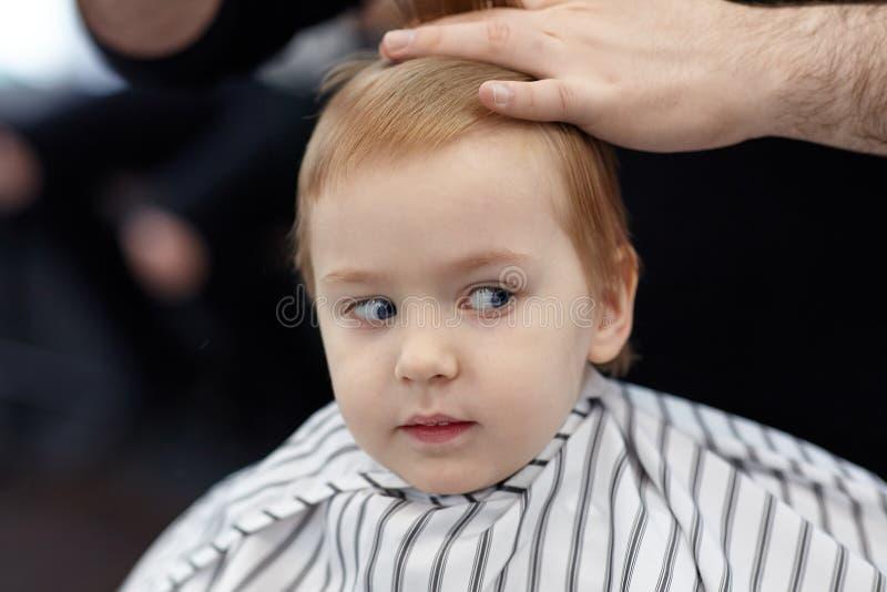 Neonato sorridente biondo sveglio con gli occhi azzurri in un negozio di barbiere che ha taglio di capelli dal parrucchiere Mani  fotografie stock
