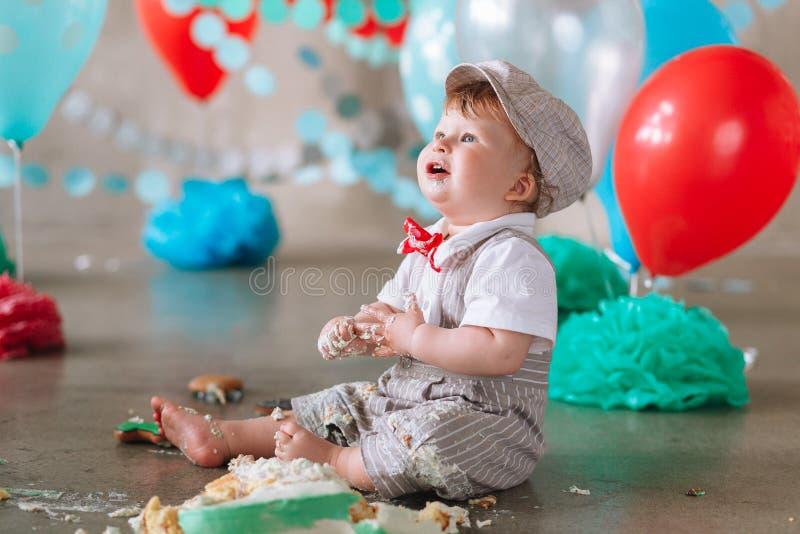 Neonato sudicio che mangia dolce sul suo primo cercare di compleanno fotografie stock