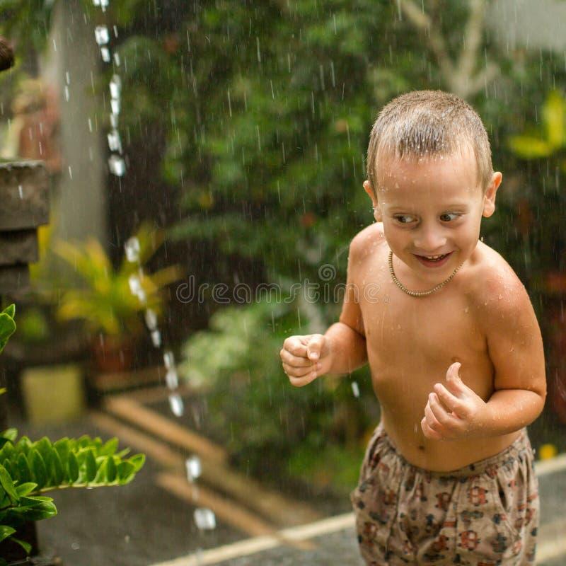 Neonato sveglio che gioca sotto la pioggia fotografia stock libera da diritti