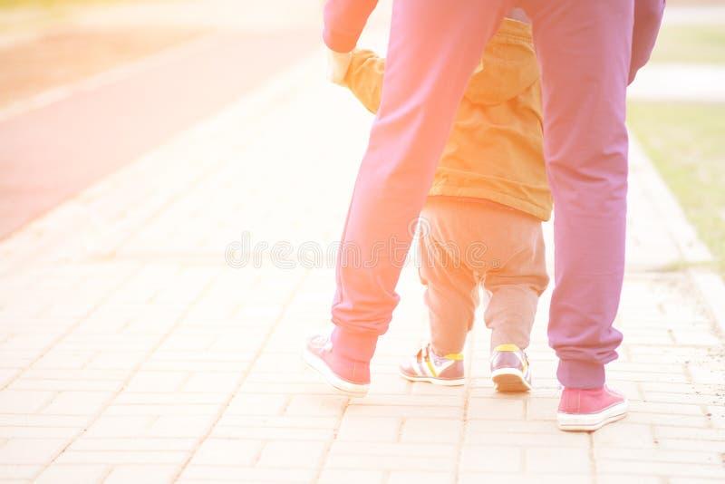 Neonato sveglio che impara camminare e fare i suoi primi punti la mamma sta tenendo la sua mano i piedi del bambino si chiudono s fotografie stock