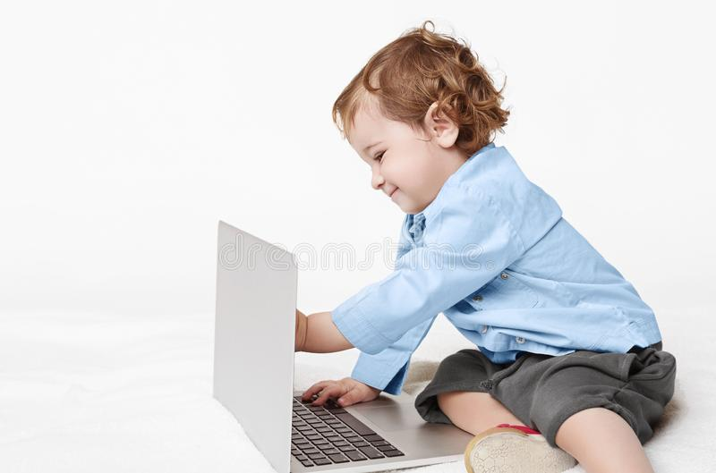 Neonato sveglio che taling con il papà sul computer portatile immagini stock libere da diritti
