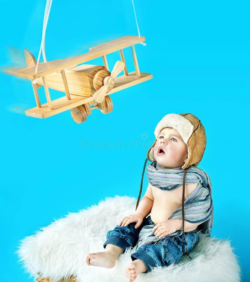 Neonato sveglio con un aereo d'annata del giocattolo immagini stock libere da diritti