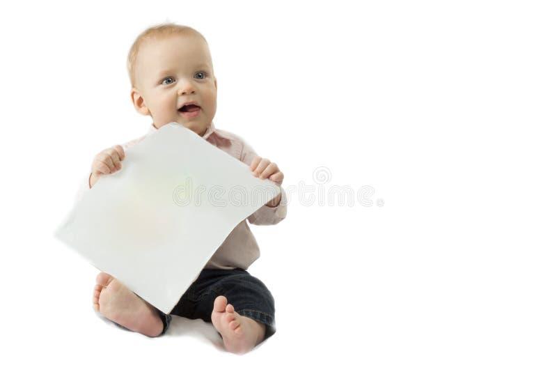 Neonato sveglio con uno strato di Libro Bianco in sue mani che si siedono nei precedenti bianchi Copi lo spazio Modello immagini stock libere da diritti
