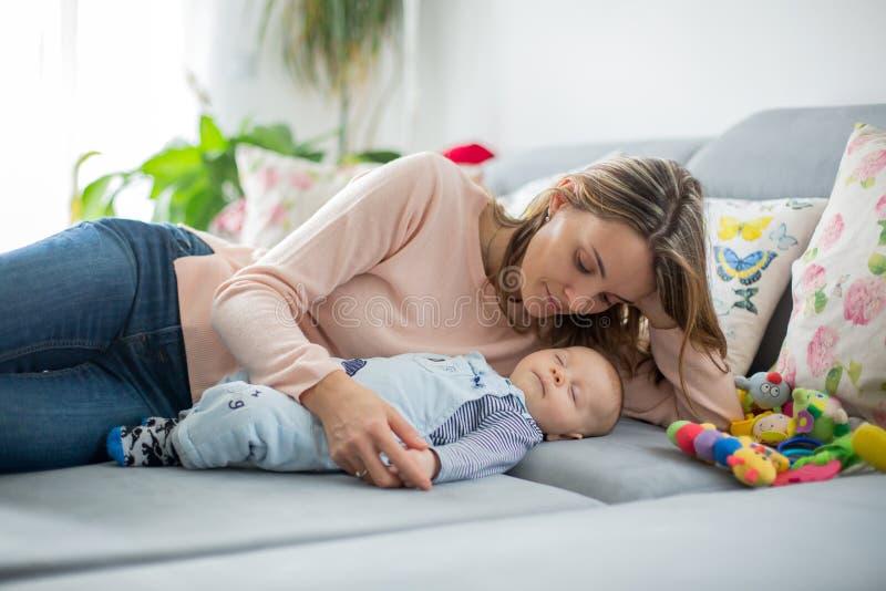 Neonato sveglio e sua la madre, trovantesi sullo strato in salone immagini stock libere da diritti