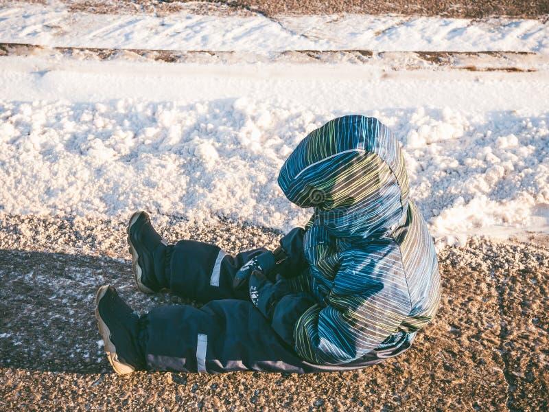 Neonato turbato che si siede sulla strada asfaltata fotografie stock