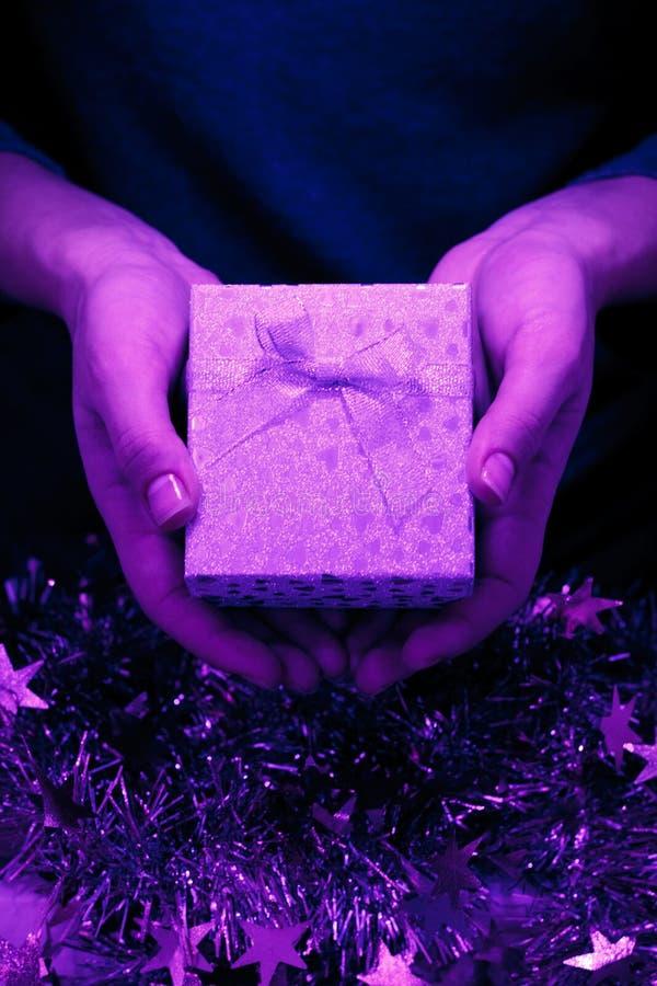Neonfarbgeschenkbox in den Händen der Frauen auf dem dunklen Hintergrund lizenzfreie stockfotografie