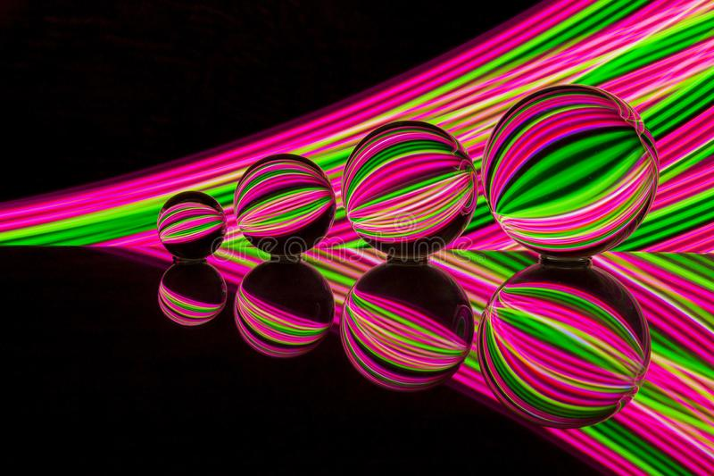 Neonglaskugel mit bunter Neonbeleuchtung hinten stockfotografie