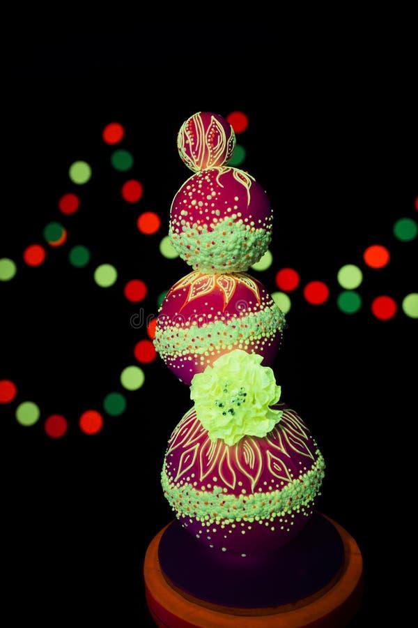 Neonowej fotografii jaskrawy kolorowy na ciemnym tle w promieniach pozafioletowy ślubny tort jarzy się fluorescencyjnych kolory obraz stock